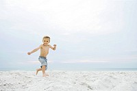 Little boy running at the beach, smiling at camera