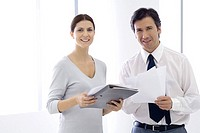 Business colleagues standing with documents and file, smiling at camera