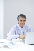 Businessman sitting at desk, smiling at camera