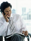 Business man on telephone looking at diary