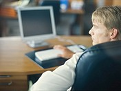 Man sitting in office with computer, looking away