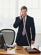 Businessman using telephone, portrait, smiling