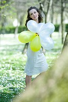 Young woman walking in meadow, holding balloons, looking away (thumbnail)