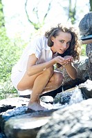 Young woman crouching on rocks, holding water in cupped hands, looking at camera