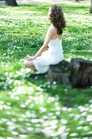 Young woman sitting in lotus position in meadow, side view, selective focus (thumbnail)
