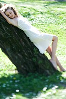 Young woman in slip leaning against tree trunk, eyes closed