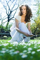 Young woman crouching in meadow, picking flowers, smiling at camera, low angle view