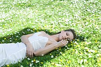 Young woman lying in meadow, touching flowers, looking away