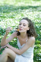Young woman sitting outdoors, blowing bubbles, looking down