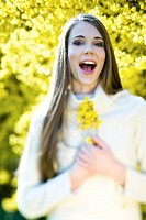 Teenage girl outdoors holding flowers, open mouth, looking at camera