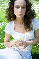Young woman sitting outdoors, holding flowers, looking at camera