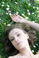 Young woman lying on the ground outdoors, looking up at camera, cropped view