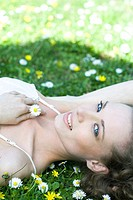 Young woman lying in grass, holding flower, smiling at camera