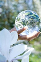 Woman holding glass sphere in hand, cropped view