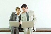 Male and female business associates, both using laptop computers, man pointing to woman´s screen