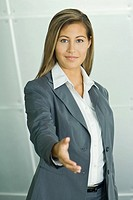 Businesswoman offering hand, smiling at camera