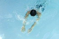 Man swimming in pool, head down, arms stretched in front of him