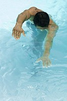 Man swimming in pool, arms out, head down