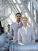 Business man and woman standing by metal construction of oil refinery