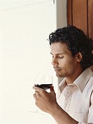 Young man sniffing glass of red wine, close_up