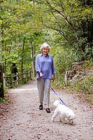 Portrait of senior woman walking dog along path in forest