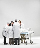 Doctors observing patient on gurney on white background