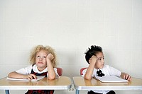 School girl and school boy 6-7 sitting in classroom