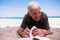 Senior man lying on beach with book, smiling