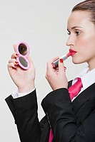 Woman in suit applying lipstick