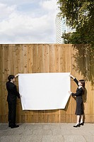 Businesspeople attaching paper to a fence (thumbnail)