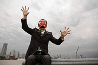 A businessman wearing a devil mask