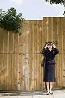 A businesswoman looking through binoculars