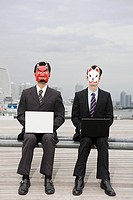Businessmen wearing masks using laptops (thumbnail)