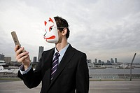 A businessman waering a mask using a cell phone