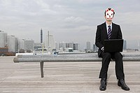 A businessman wearing a mask using a laptop