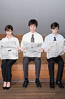 Businesspeople reading a newspaper