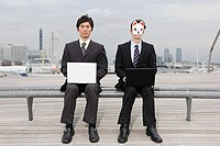 Businessmen wearing masks using laptops