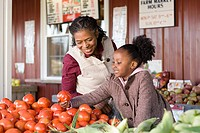 A grandmother and granddaughter choosing tomatoes (thumbnail)