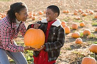 A grandmother and grandson holding a pumpkin
