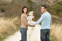 Couple holding hands on a dirt track