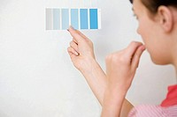 Young woman holding colour chart