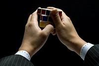 Man`s hand playing Rubik`s cube