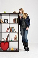 Woman leaning against bookshelf with book