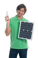 Man holding energy-saving bulb and solar panel (thumbnail)