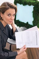 Businesswoman with utility invoice sitting in front of computer