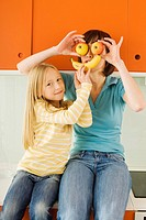 Mother and daughter 8_9 in the kitchen, mother holding apples in front of her eyes
