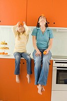 Mother and daughter 8_9 in the kitchen, balancing orange on head, looking up