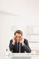 Businessman sitting at desk, hands to head