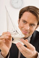 Businessman holding a model ship, portrait