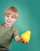 A cute 3 1/2 year old Caucasian boy holding a pear.